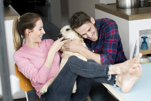 Happy young couple cuddling with dog at home - PESF00823