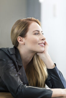 Portrait of smiling young woman wearing leather jacket - PESF00829