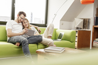 Smiling young couple on couch in living room at home sharing tablet - PESF00832
