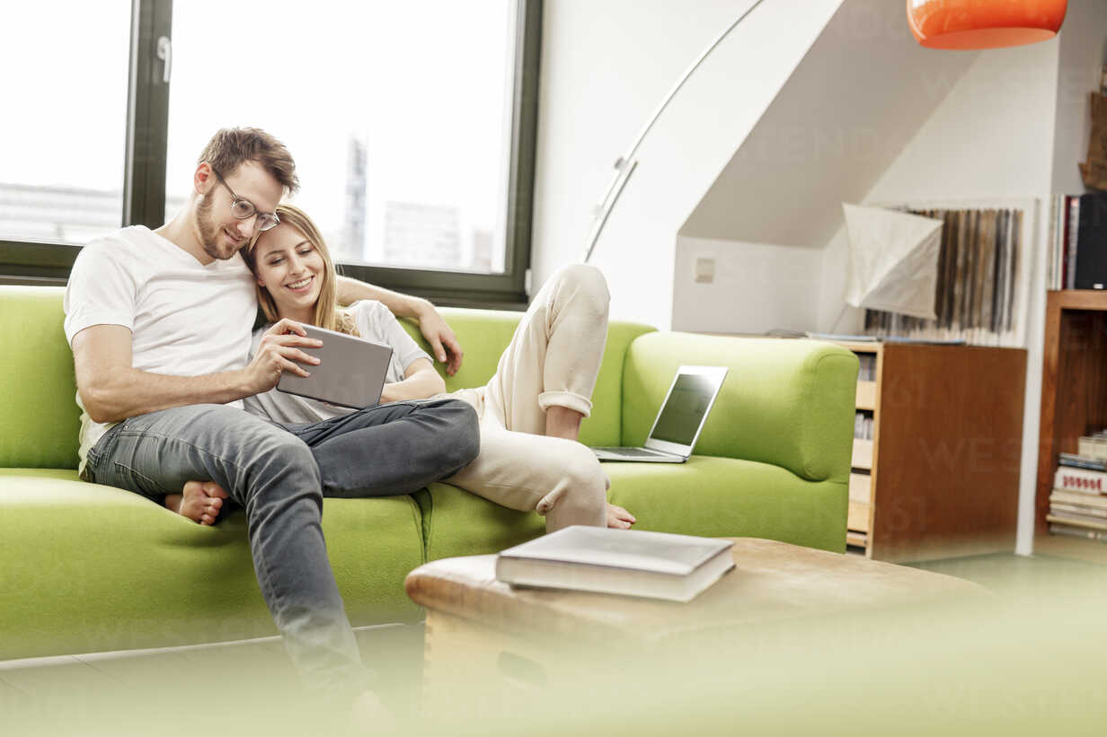 Smiling young couple on couch in living room at home sharing tablet - PESF00832 - Peter Scholl/Westend61