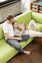 Smiling young couple on couch in living room at home sharing cell phone - PESF00835
