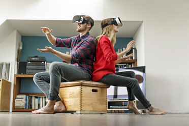 Young couple at home sitting on box wearing VR glasses - PESF00841
