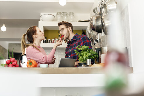 Young couple with tablet tasting vegetable in kitchen - PESF00844