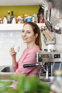 Smiling young woman with cup of espresso in kitchen at home - PESF00850