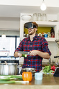 Happy young man wearing VR glasses cooking in kitchen - PESF00853