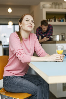 Smiling young woman with glass of orange juice in kitchen at home with man in background - PESF00856