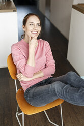 Portrait of smiling young woman sitting on wooden chair at home - PESF00859