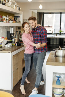 Happy young couple dancing in the kitchen - PESF00862