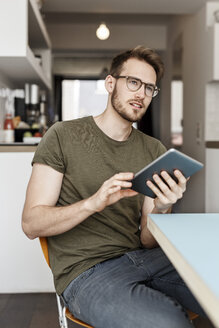 Young man with tablet sitting in kitchen at home - PESF00868