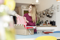 Smiling young woman at home unpacking parcel with clothing - PESF00871