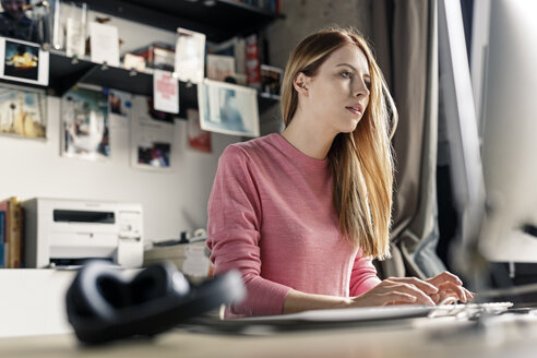 Young woman working on computer at desk at home - PESF00877