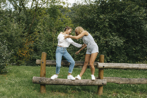 Two happy young women balancing on fence in a park - KNSF03055
