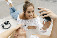 Two happy young women sharing cell phone in a skatepark - KNSF03067
