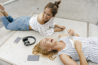 Two happy young women lying on ramp in a skatepark making music - KNSF03070