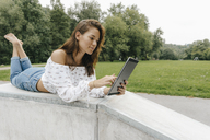 Young woman using lying in a skatepark using a tablet - KNSF03073