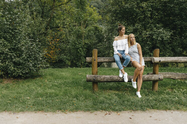 Two young women sitting on fence in a park - KNSF03076