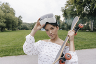 Portrait of young woman with VR glasses holding skateboard - KNSF03082