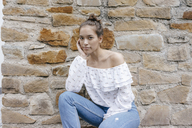 Portrait of young woman at natural stone wall - KNSF03085