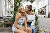 Young woman kissing female friend in the city - KNSF03088