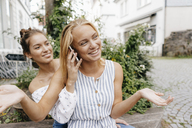 Two happy young women with cell phone in the city - KNSF03091