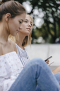 Young woman with friend sitting down holding cell phone - KNSF03106
