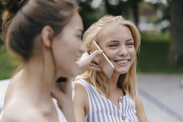Two happy young women with cell phone outdoors - KNSF03109