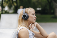 Young woman with headphones listening to music outdoors - KNSF03112