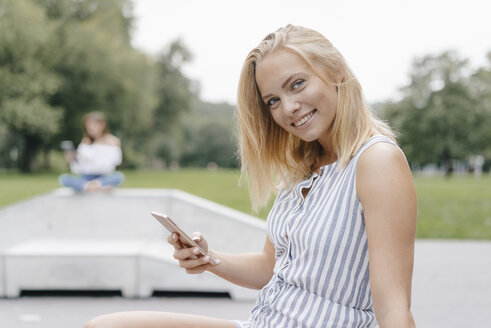 Portrait of smiling young woman with cell phone in a skatepark - KNSF03118