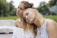Young woman resting on female friend's shoulder - KNSF03130