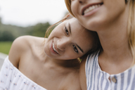 Smiling young woman resting on female friend's shoulder - KNSF03133