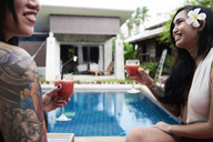Two happy women drinking cocktails at swimming pool - IGGF00232