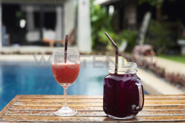 Two fruity cocktails at the poolside in rain - IGGF00238