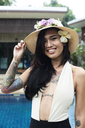 Portrait of smiling woman with flower in her hair wearing a straw hat at a swimming pool - IGGF00241