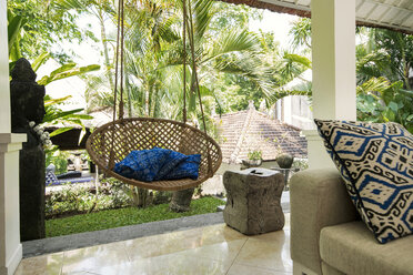 Open living area in a tropical luxury home with couch and hanging chair - SBOF00922