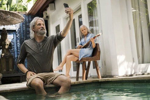Senior man taking selfie at poolside while his wife is playing the guitar - SBOF00943