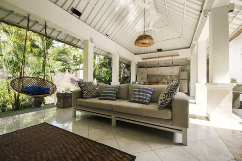 Open living area in a tropical luxury home with couch and hanging chair - SBOF00955