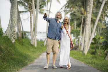 Handsome senior couple strolling through tropical landscape with palm trees - SBOF00958