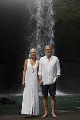 Affectionate senior couple standing in front of tropical waterfall - SBOF00961