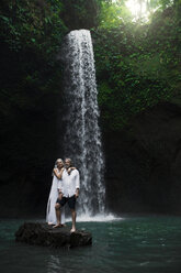 Affectionate senior couple standing in front of tropical waterfall - SBOF00964