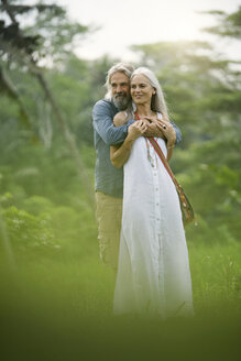 Handsome senior couple hugging in tropical landscape - SBOF00970