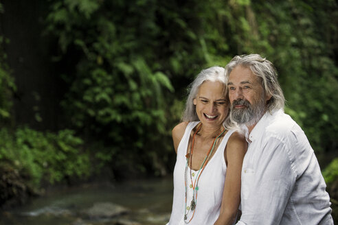 Handsome senior couple smiling in tropical jungle - SBOF00973