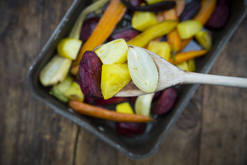 Oven winter vegetables, carrot, beetroot, potato and parsnip in roasting tray, on wooden spoon - LVF06483
