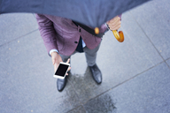 Businessman standing under umbrella holding cell phone, partial view - BSZF00100