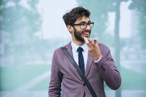 Portrait of happy young businessman on the phone outdoors - BSZF00103