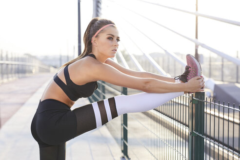 Young athletic woman stretching her legs after urban workout - BSZF00108