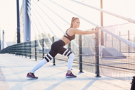 Young athletic woman stretching on the bridge - BSZF00111
