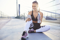 Athletic woman drinking water and checking her phone after workout - BSZF00117