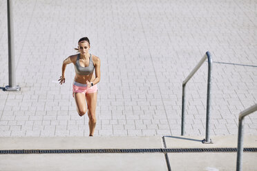 Fit young woman running on stairs - BSZF00126
