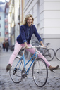 Blond woman riding a bike in the city - PNEF00373