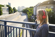 Portrait of smiling young woman listening music with headphones - KNSF03145